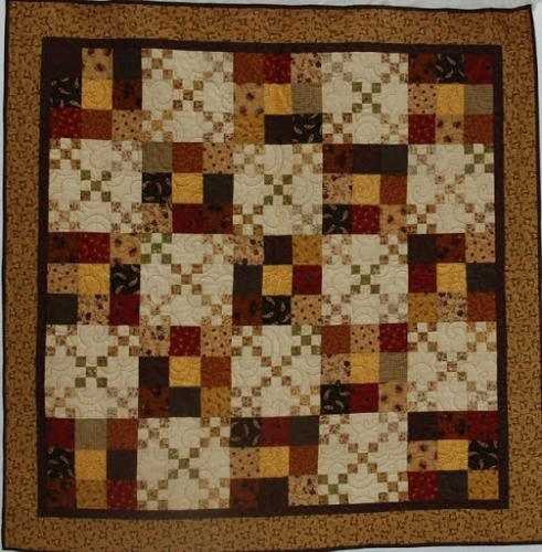 This double 9-patch by Audrey Woods has been quilted edge to edge with Popcorn , a very popular design by Jodie Beamish of Willow Studios