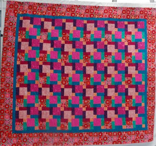 This patchwork design is called Split 9-patch or Hidden 9-patch. its is made with Kaffe Fassett fabrics and quilted with the Hearts a Flutter design by Jodie Beamish