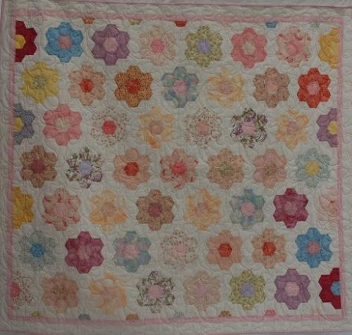 Pastel hexagons by Audrey Woods edge to edge quilted with a design called Daisy Creeper by Jodie Beamish