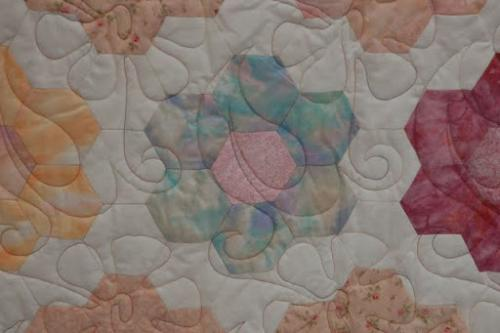 This is a detail of Daisy Creeper on Audrey Woods Pastel Hexagons quilt