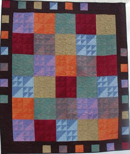 This quilt has been made with Oakshott fabrics and is edge to edge quilted with a design called Seaside Swirl