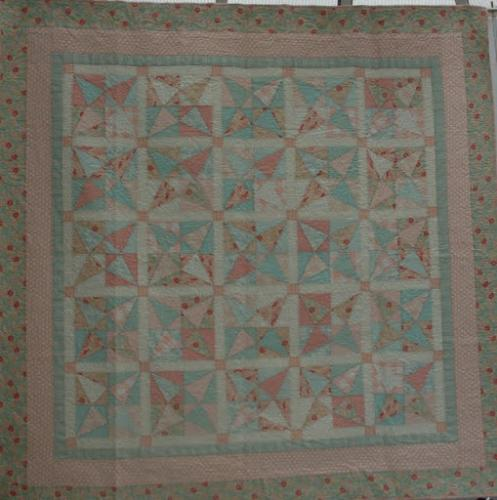 Crossed Canoes by Lisa Price. This beautiful quilt has an interesting tucked fabric as an inner border so I worked an edge to edge design-Rhapsody- in the centre with a border design of Asian Clouds in the outer borders. The pintucked border was stitched int he ditch
