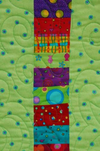 This is a detail of the back of New York Beauty , showing the interesting use of spare fabrics from the front of the quilt combined into an eyecatching accent strip on the back