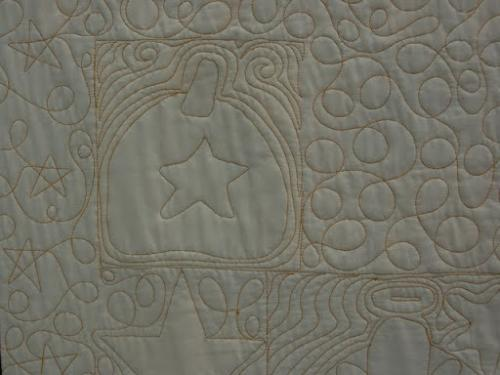 Detail of reverse of Halloween block quilt showing various meandering styles