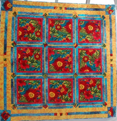 This quilt is called Piece of Paradise and is an original design based on a simple 9-patch, pieced and quilted by Isabel Hall. It is edge to edge quilted with a pattern by Linda Taylor called Feather Rose Collection II