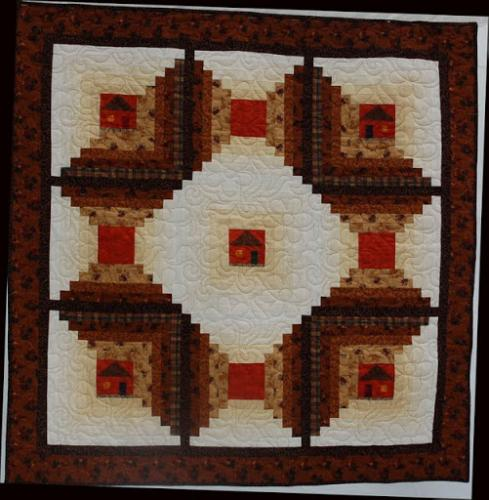 Log Cabins by Audrey Woods. The block centres are small pieced cabins and the quilting design is Daisy Swirl by Jodie Beamish